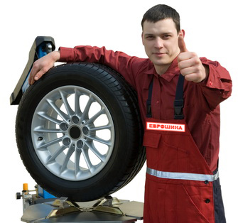 Handsome young car mechanic with wheel
